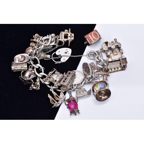 1 - A SILVER CHARM BRACELET, suspending twenty-four charms such as a hinge open church, opens to reveal ...