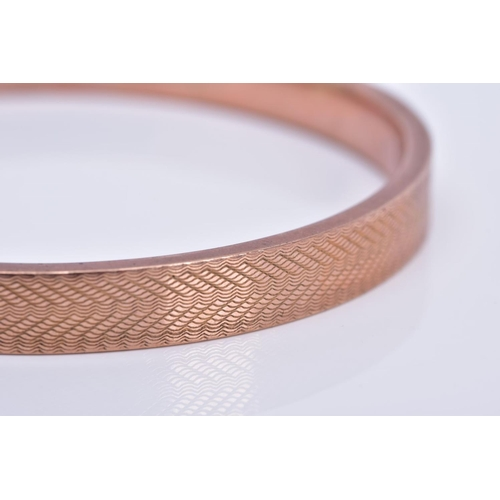 55 - AN EARLY 20TH CENTURY ROSE GOLD SLAVE BANGLE, engine turned design, measuring approximately 78mm in ...
