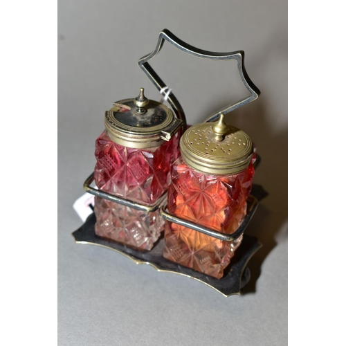 551 - A LATE VICRORIAN CRANBERRY GLASS CRUET IN A SILVER PLATED FRAME, on three ball feet...