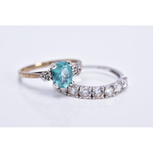 6 - TWO 9CT GOLD GEM SET DRESS RINGS, the first set with an oval cut topaz flanked with illusion set sin...