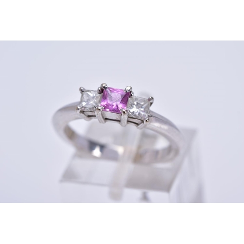 73 - A MODERN 18CT WHITE GOLD PINK SAPPHIRE AND DIAMOND THREE STONE RING, a square cut pink sapphire meas...