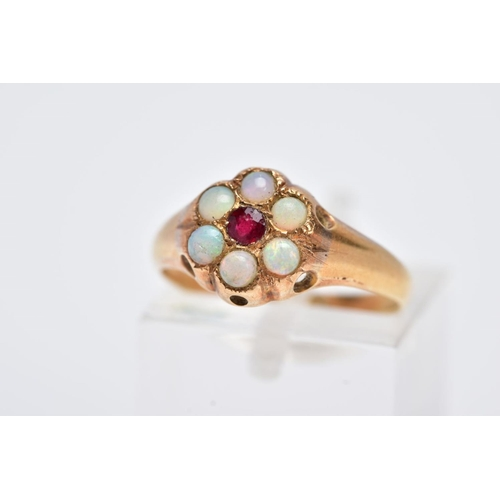 12 - A YELLOW METAL OPAL CLUSTER RING, designed with a central circular cut red stone assessed as paste, ...