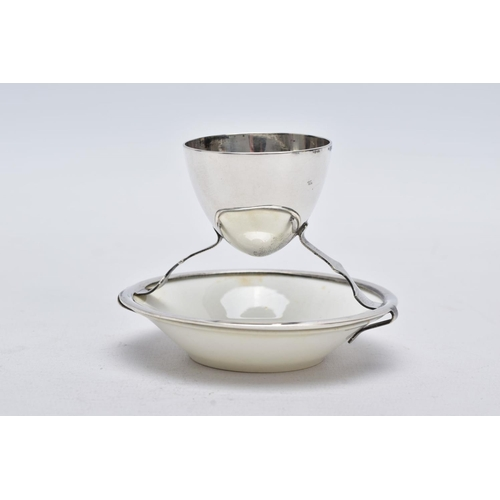 3 - A GEORGE V SILVER AND CERAMIC EGG CUP, designed with a plain polished egg cup hallmarked 'Hukin & He...