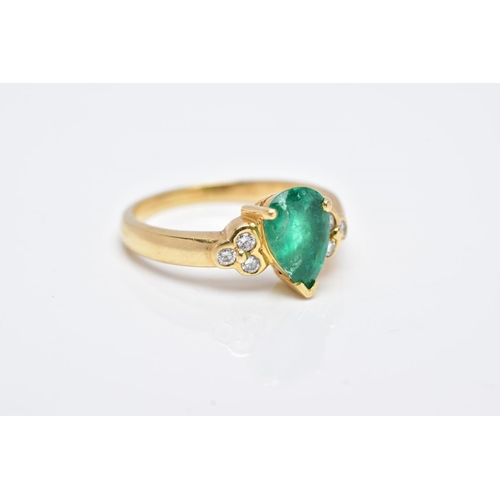 41 - A YELLOW METAL EMERALD AND DIAMOND RING, designed with a central claw set, pear cut emerald, flanked...