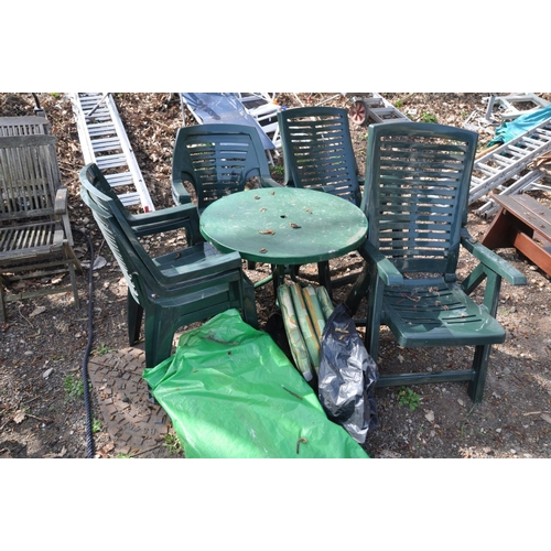 1007 - A GREEN PAINTED METAL CIRCULAR GARDEN TABLE on shaped legs together with four green plastic stacking...