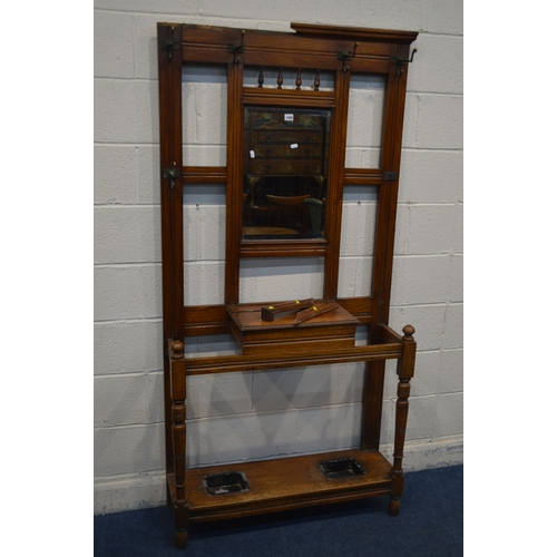 1072 - AN EDWARDIAN WALNUT HALL STAND, with six hooks but one hook missing, central bevelled mirror, hinged...