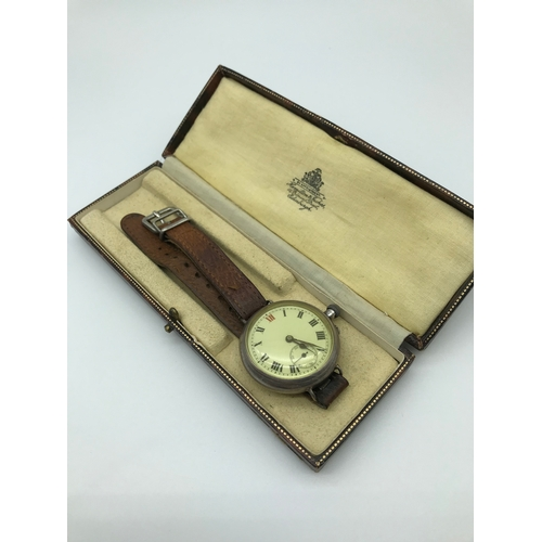 13 - A silver antique gentleman's wrist watch, on a leather strap, in running order, fitted in a Hamilton...