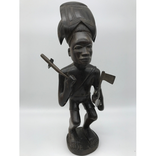 20 - Carved Ebony African tribal figure. Holding axe, tool and has a sword. Stands 33cm in height...