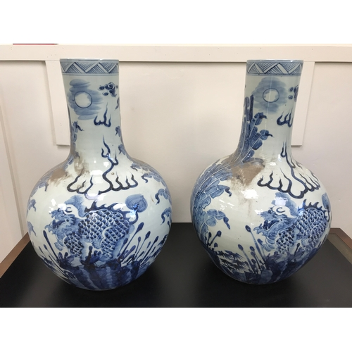 29 - 2 Large Antique Blue and White oriental bottle neck vases, Designed with dragon faced foo dogs. Stan...