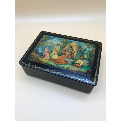 10 - Fedoskino Pegockuho Russian hand painted and lacquered box. Measures 5.5x17.3x12.3cm...