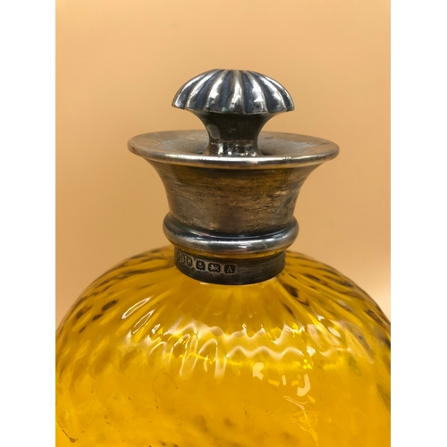 30 - A fine example of an amber decanter topped with a Birmingham silver rim. Comes with an ornate stoppe...