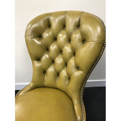 30A - An antique Chesterfield mustard leather smokers spoon back parlour chair....