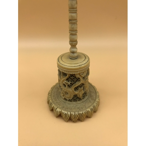 22 - Victorian carved puzzle ball and stand done in an oriental manner. Stands 20cm in height...