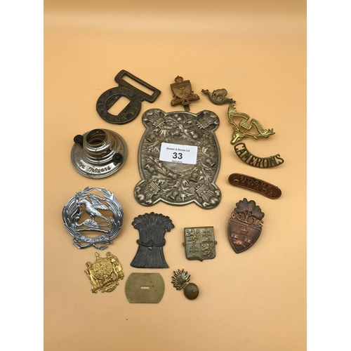 33 - A Tub full of mixed military cap badges, buckles and thistle design plaque...