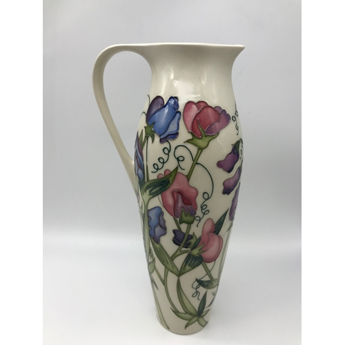 30 - A Large Moorcroft (2nd) waterjug/ claret jug. Styled with flowers. Has a firing/hairline crack to th...