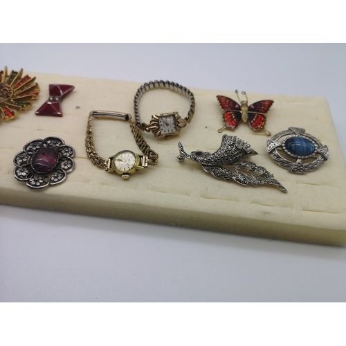 36 - A quantity of nine decorative brooches together with a gold cased ladies Rotary watch with rolled go...
