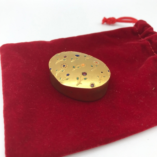 36 - A Small gilt metal pill box decorated with enamelled flowers....