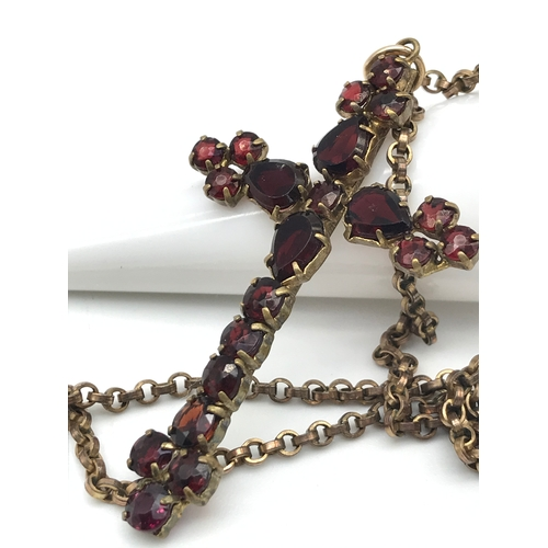 29 - An antique gilt metal and Garnet stone set cross pendant with gilt metal chain. Pendant measures 5cm...