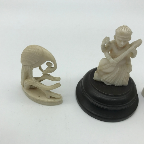 35 - 3 early 1900's hand carved ivory figures. Includes a god figure sat upon a wooden base. Measures 6cm...