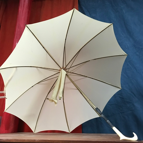 299 - A Ladies Antique Tolido parasol in ivory white, Styled with Ivory handle and comes with cover....
