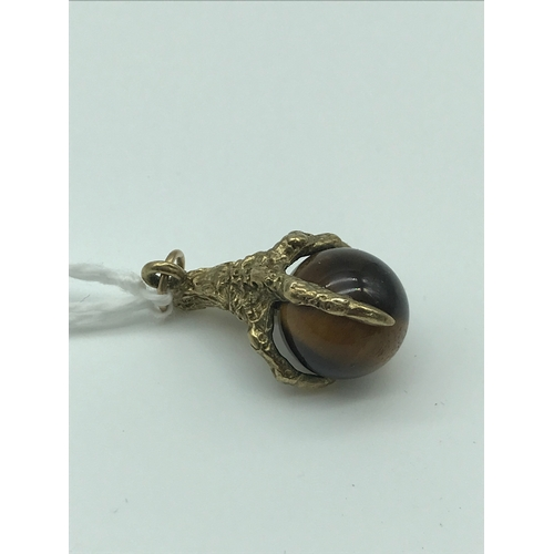 6 - A 9ct gold claw and tiger eye stone pendant. Weighs 4.76grams...