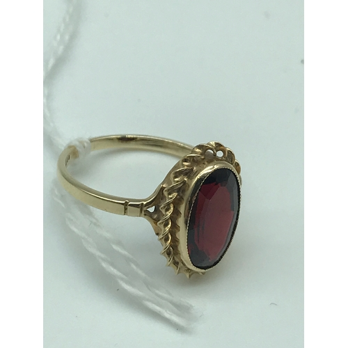 11 - A Beautiful example of a ladies 9ct gold ring set with a large oval shaped Garnet stone. Size N...