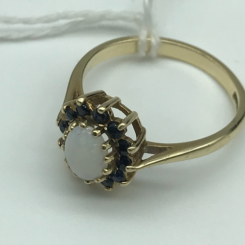 24 - A Beautiful 9ct gold ladies ring set with a single opal and surrounded by a Sapphire cluster. Size N...