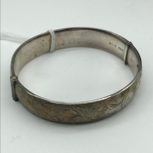 27 - A Birmingham silver bangle, ornately engraved....