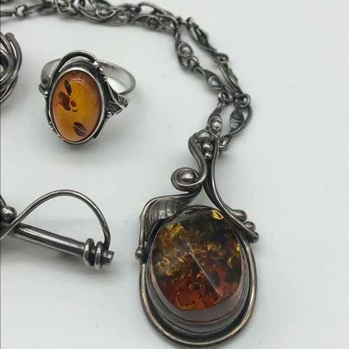 28 - A Beautiful  Silver and Amber set. Includes Ornate pendant with necklace, 2 Brooches and ring....
