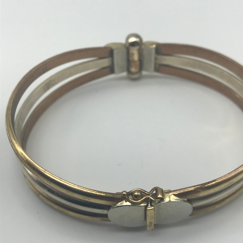 13 - A 9ct gold two tone ladies bangle, Weighs 23.98grams...