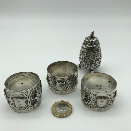 32 - Indian silver pepper pot and three matching napkin rings...