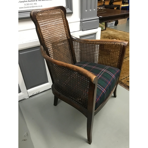 205a - An early 20th century bergere side and back bedroom chair upholstered with tartan material...