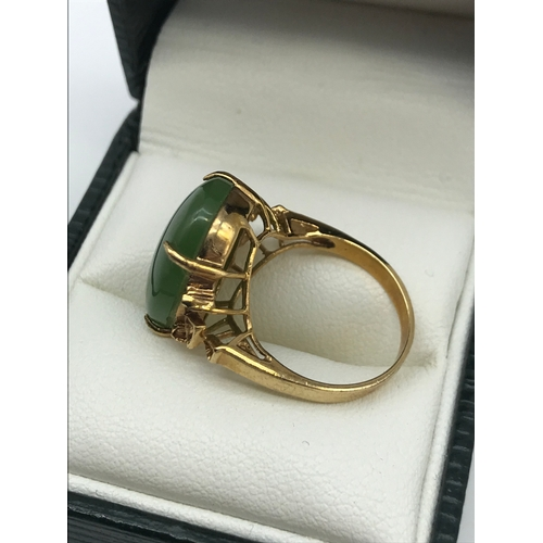 16 - An antique gold ring set with a large oval shaped jade stone, Ring size J, Weighs 3.60 grams, Stone ...