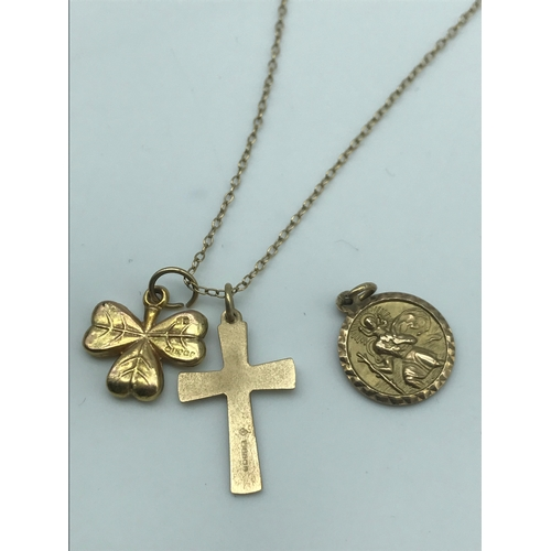 28 - A 9ct gold necklace with three various charms, Cross, St Christopher & Shamrock, weighs 3.60grams...
