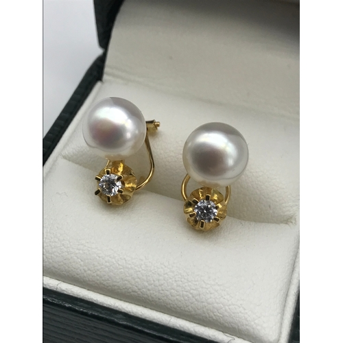 36 - A Pair of 18ct gold earrings set with a single large pearl and single clear stone. Total weight 4.42...