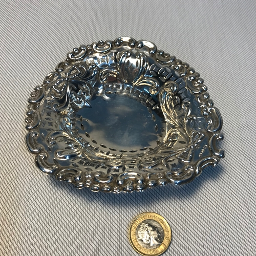 23 - A Birmingham silver pierced dish supported on three bun feet, made by Colen Hewer and dated 1896. Me...