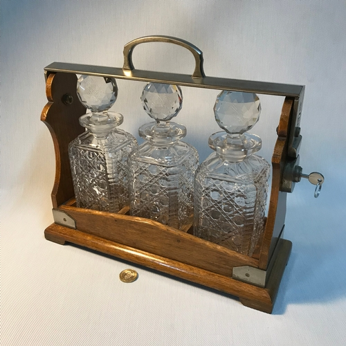 30 - Antique oak and plated Tantalus Betjemann's Patent 36682 London, Fitted with three crystal decanters...