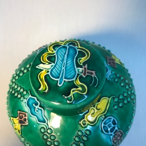 40 - A Chinese enamel painted preserve pot, depicting raised designed flowers, beads and birds. Has a Kan...