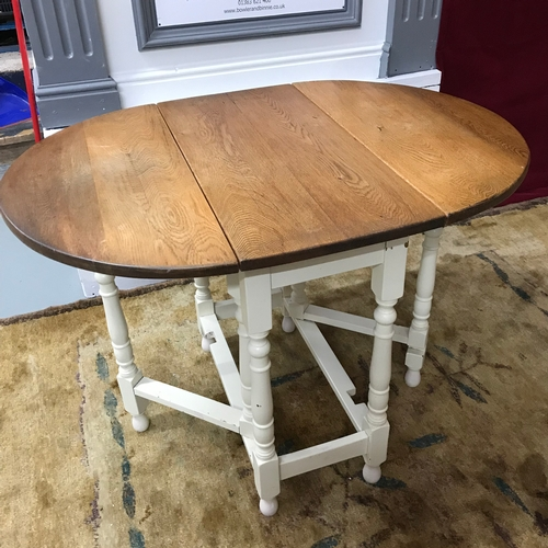 125A - A Solid light oak topped, drop end dining table. Painted white base leg supports. Fully extended it ...