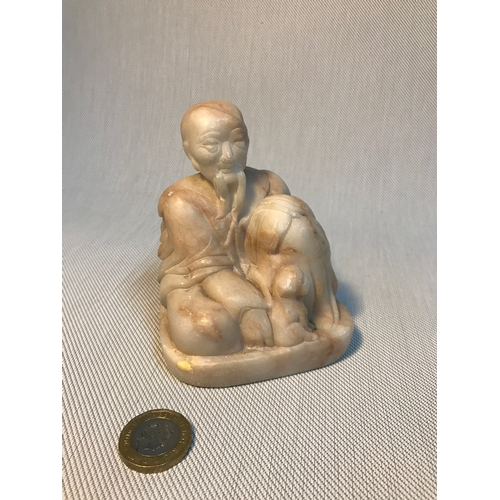 62 - Antique Chinese Monk sitting with small dog hand carved marble figure. Measures 10cm in height...