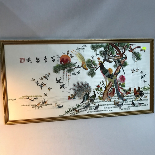 75B - An oriental silk tapestry depicting various exotic birds.Hand stitched signature, Gilt frame measure...