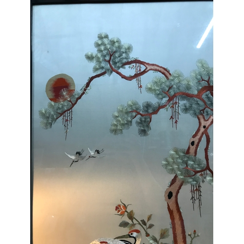 95B - A Large Antique Oriental silk tapestry depicting two storks under a tree. Frame measures 100x52cm...