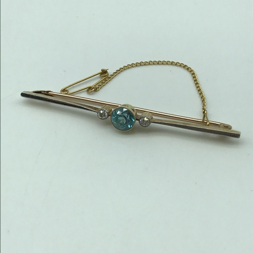 6J - A Gold unmarked bar brooch set with a large sky blue topaz with two large side Diamonds. Weighs 5.53...