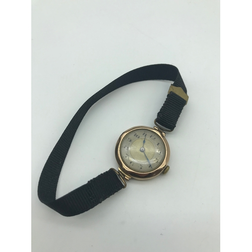 8J - A Vintage 9ct gold watch in a working condition. Has a black material strap....