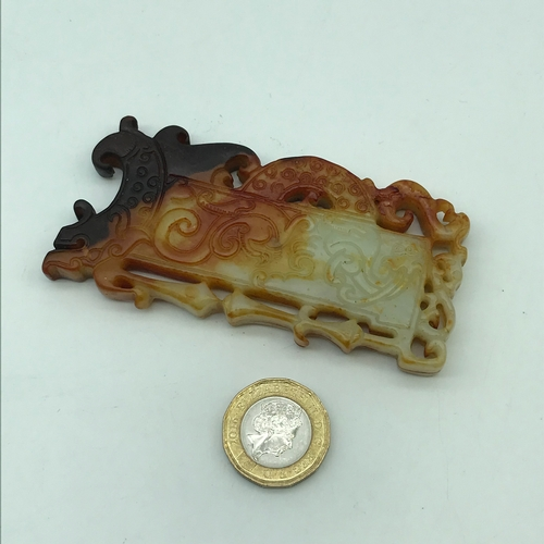 16J - A Finely carved Chinese jade token/ pendant showing dark brown tinges. Measures 9cm in length...