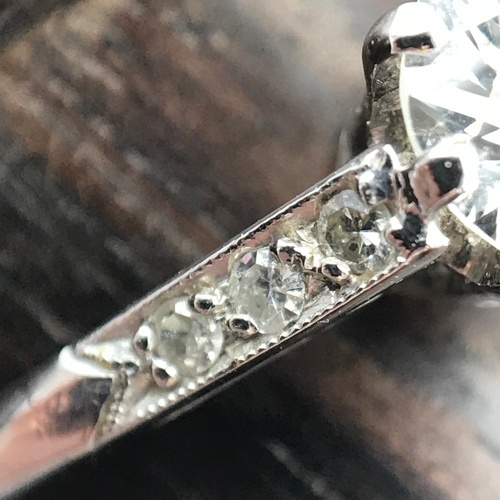 20J - An Antique ladies 14ct white gold ring set with large single diamond off set by three diamonds to ea...