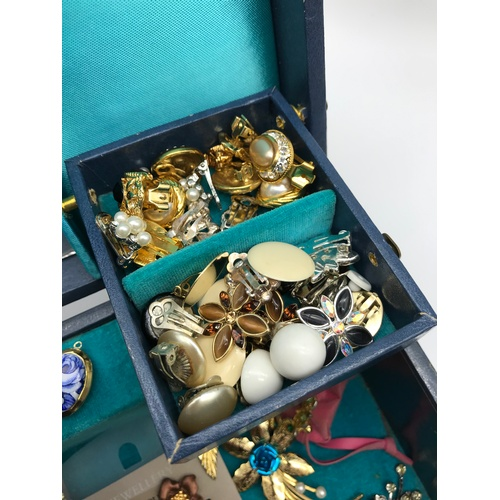 24J - A Vintage jewellery box containing a quantity of vintage costume jewellery to include clip on earrin...