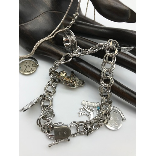 26J - A heavy Sterling silver charm bracelet with various charms, Silver baby bangle and silver necklace...