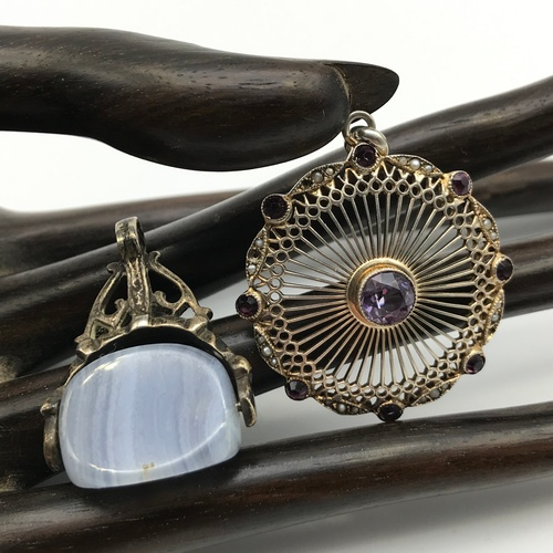 33J - A 900 grade silver Art Nouveau style pendant designed with centre Amethyst off set by smaller Amethy...