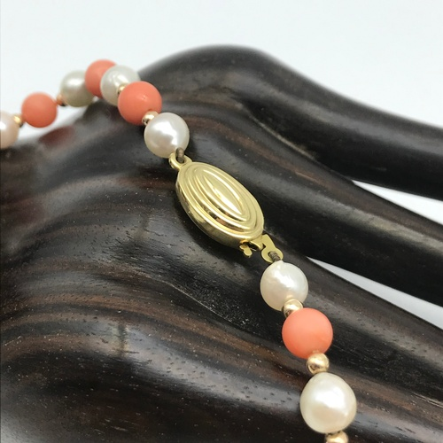 42J - Two vintage sets of pearl necklaces designed with 9ct gold clasps. One is designed with coral pink s...